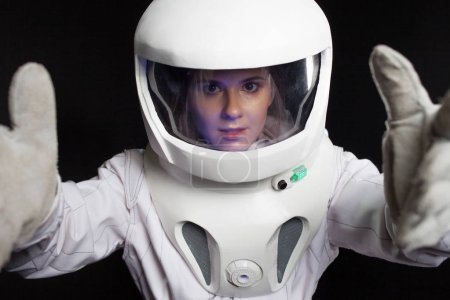 Astronaut on a black background in space. Portrait of a young woman in a helmet. space explorers.