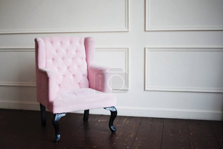 Pink armchair against wall. Perspective distortion and free space