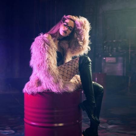 Young attractive woman with stylish clothes. Beautiful girl in fluffy pink fur coat sits on barrel. Neon light