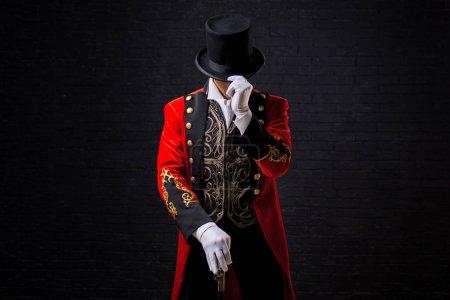 Photo pour Showman. Jeune artiste, présentateur ou acteur sur scène. Le type au camisole rouge et au cylindre. Regarde en bas, main sur le chapeau - image libre de droit
