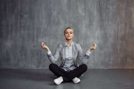 Young woman in business suit sitting in Lotus pose, restore energy, meditate. Health and work