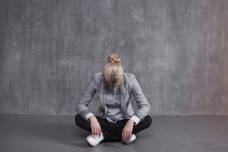 Fatigue, professional burnout. Young woman in business suit sitting in Lotus pose, head down