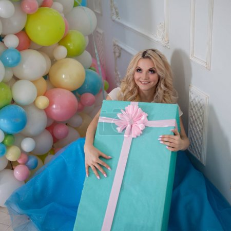 Funny and beautiful blonde with huge gift box. Charming young woman in a curvy blue skirt.