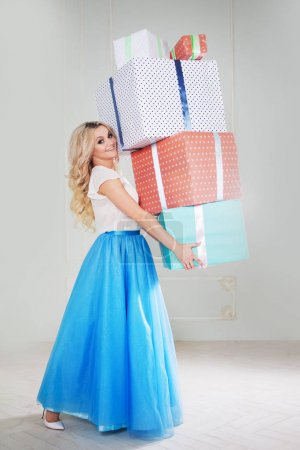 Funny and beautiful blonde with a bunch of big gift boxes. Charming young woman in a curvy blue skirt.