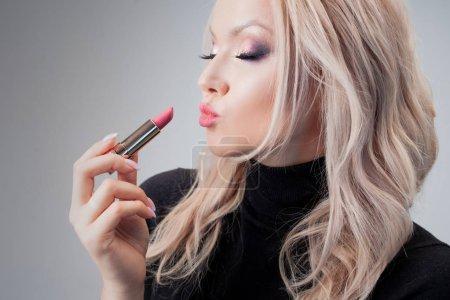 Photo pour Charming blonde salope with sloppy curls, use the lipstick gentle red hue. portrait de près - image libre de droit