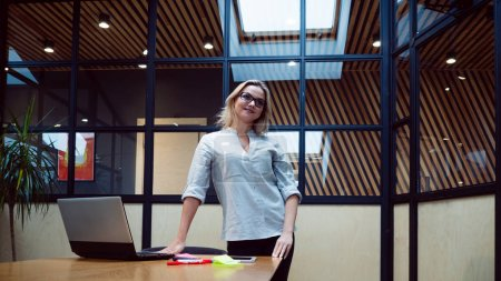 Foto de Mujer joven empresaria en su oficina. Trabajo en la oficina, una chica profesional se encuentra cerca de la mesa con un ordenador portátil, datos actuales y personal de tren. - Imagen libre de derechos
