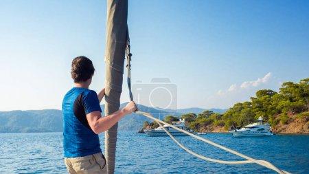 homme en t-shirt bleu se tient sur le pont près de la voile, voile et yachting, concept .