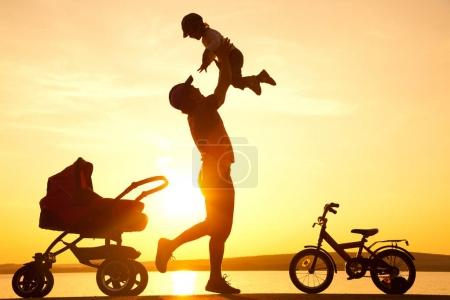 Photo for Happy dad  daughter throws up into the sky next to the stroller at sunset - Royalty Free Image