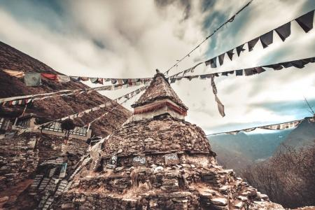 Prayer flags and buddhist stupa on trekking route