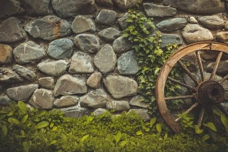 Stone wall texture background with ancient wheel