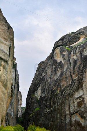 Photo pour Tightrope walker marche le long d'une corde raide tendue entre les deux hautes roches contre un ciel nuageux dramatique à Meteora, Grèce - image libre de droit