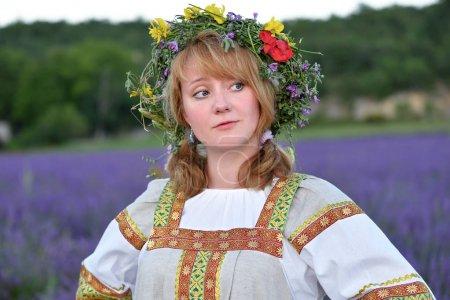 Photo pour Fille paysanne dans une couronne de fleurs vêtue d'un vêtement russe traditionnel se tient dans le champ de lavande - image libre de droit