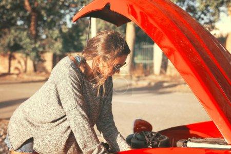 Photo pour Femme sur une route ayant un problème avec sa vieille voiture - image libre de droit