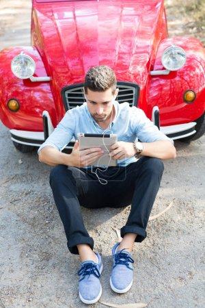 Young man resting at car