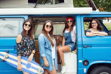 Young hippie women traveling by car