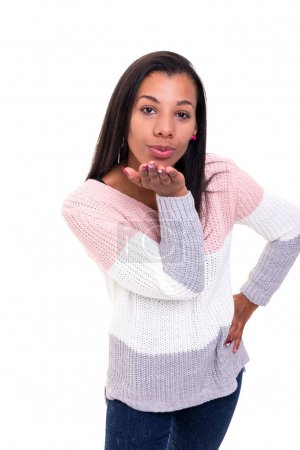 Beautiful African young woman blowing kiss, isolated over white background
