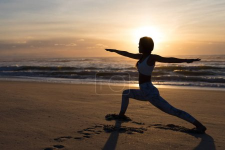 Silhouette of sporty young woman doing yoga practice at beach, concept of healthy life and natural balance between body and mental development