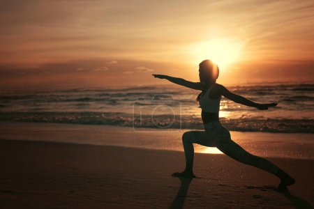 Sporty young woman doing yoga practice at the beach , concept of healthy life and natural balance between body and mental development
