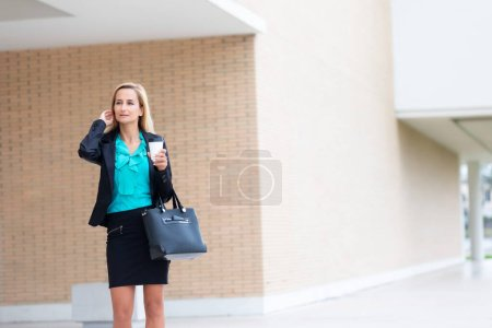 Photo pour Femme d'affaires avec café et parler au téléphone près du Bureau - image libre de droit