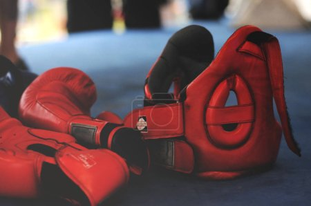 Red Boxing Gloves and Headgear on Boxing Ring.