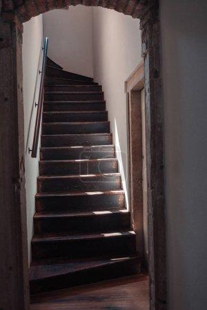 Photo pour Escalier sombre en bois dans une vieille maison. Murs en plâtre blanc. Retour de la lumière d'une fenêtre d'en haut. Barre métallique neuve - image libre de droit