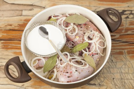 raw rabbit on a wooden Board with ingredients for stewing onion,