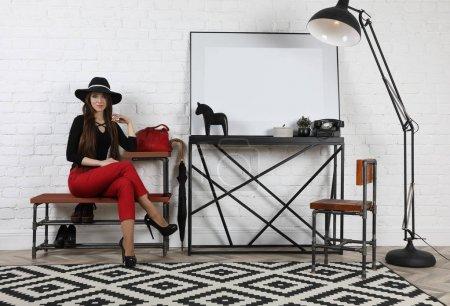 Photo pour Jolie jeune fille dans un chapeau noir et pantalon rouge assis sur un banc dans le studi - image libre de droit