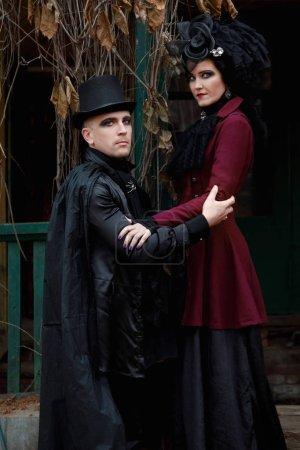 Photo pour Portrait d'un couple mignon vêtu de vêtements à l'ancienne dans le style vampire sur le porche d'un vieux mansio envahi - image libre de droit