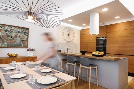 Photo pour Intérieur d'une cuisine et d'une salle à manger où une fille pose la table en motio - image libre de droit
