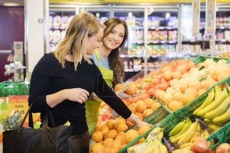 Happy Saleswoman Standing By Female Customer Choosing Oranges