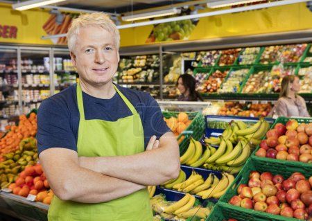Smiling Salesman Standing Arms Crossed By Fruits In Store