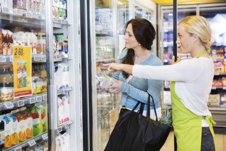 Saleswoman Showing Products To Female Customer In Refrigerator
