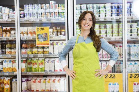 Photo for Portrait of confident mature saleswoman standing with hands on hip against products displayed in refrigerator - Royalty Free Image
