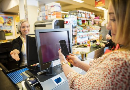Cashier Gesturing While Female Customer Doing NFC Payment