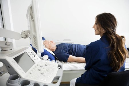 Doctor Looking At Monitor During Ultrasound Examination In Hospi
