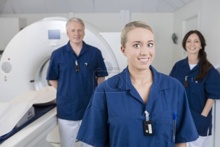 Smiling Medical Professional With Colleagues Standing By MRI Mac