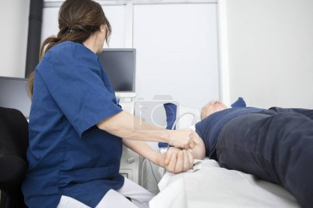 Doctor Using Ultrasound Probe On Males Hand In Hospital