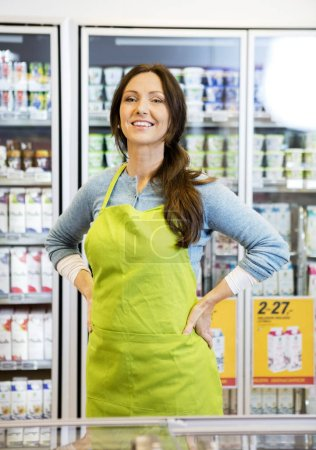 Photo for Portrait of confident mature saleswoman with hands on hip against products displayed in refrigerator - Royalty Free Image