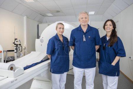 Confident Medical Team Smiling By MRI Machine