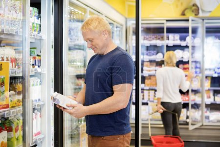Male Customer Holding Juice Packet In Grocery Store