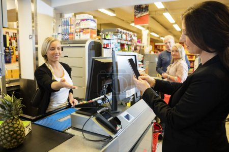Cashier Gesturing While Customer Doing NFC Payment