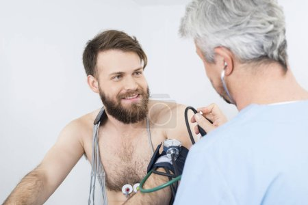 Patient Looking At Doctor Checking Blood Pressure