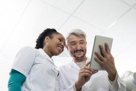 Doctors Using Digital Tablet In Examination Room