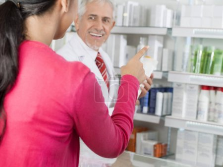 Customer Pointing At Products While Chemist Looking At Her