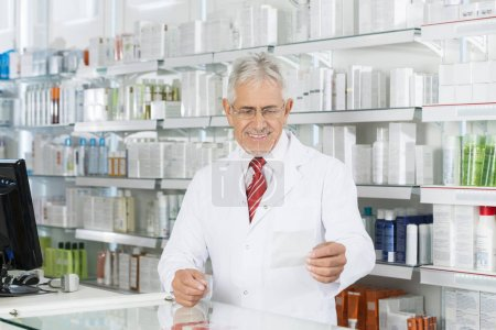 Chemist Looking At Prescription Paper At Counter