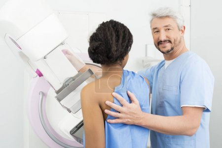 Portrait Of Doctor Assisting Patient Undergoing Mammogram Test