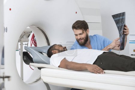Male Doctor Showing X-ray To Patient Lying On CT Scanner