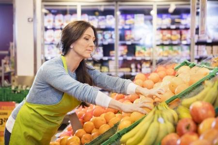 Photo for Beautiful mature saleswoman arranging oranges in supermarket - Royalty Free Image