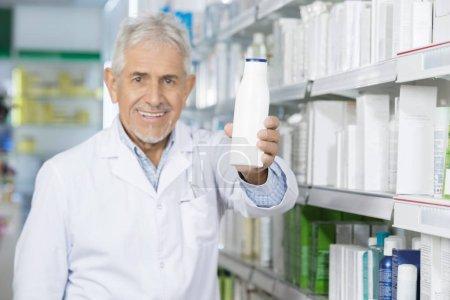 Smiling Pharmacist Holding Shampoo Bottle In Pharmacy