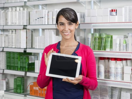 Woman Holding Tablet Computer With Blank Screen In Pharmacy
